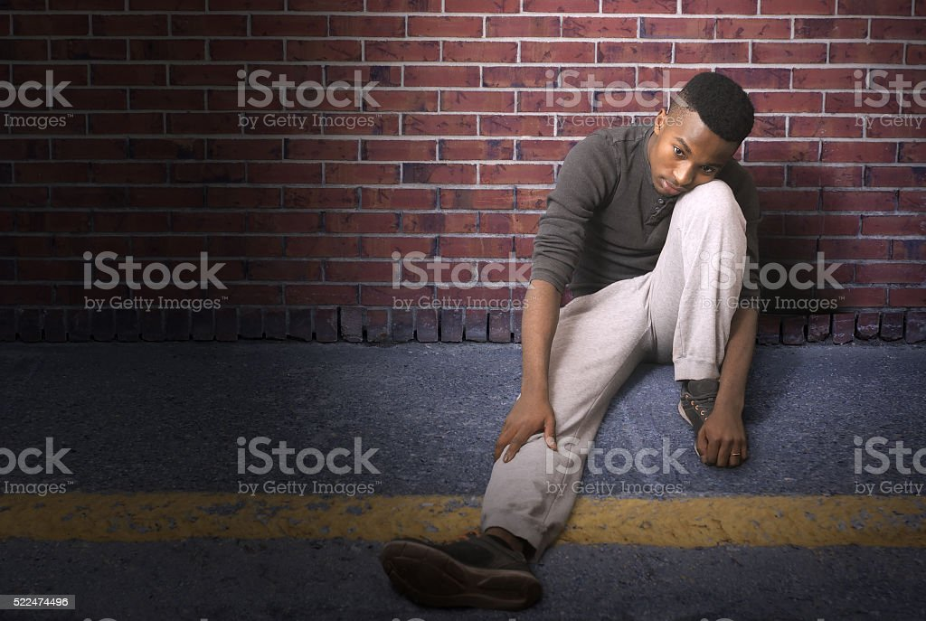 young man sitting on the ground at night stock photo