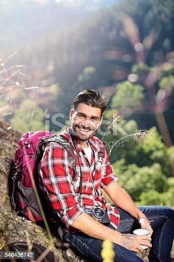 istock Young man sitting on the rock and drinking coffee 546438742