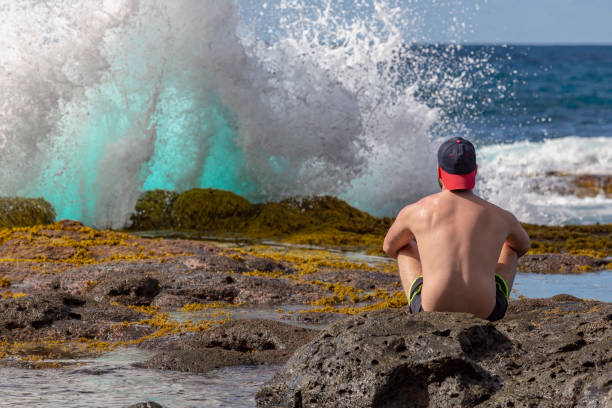 A young man sitting on the rocks and looking at the ocean while a big wave is breaking in front of him stock photo