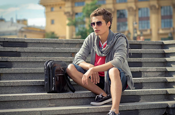 Young man sitting on the stairs stock photo