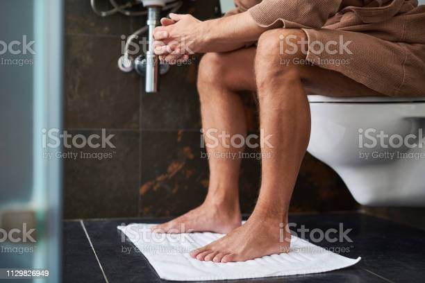 Young Man Sitting On Toilet Stock Photos & Young Man