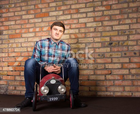 496487362istockphoto Young Man Sitting on Vintage Toy Vehicle 478863704