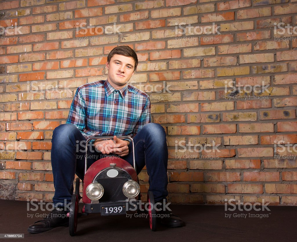 Young Man Sitting on Vintage Toy Vehicle stock photo