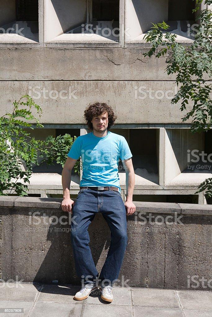 Jeune homme assis sur un mur photo libre de droits