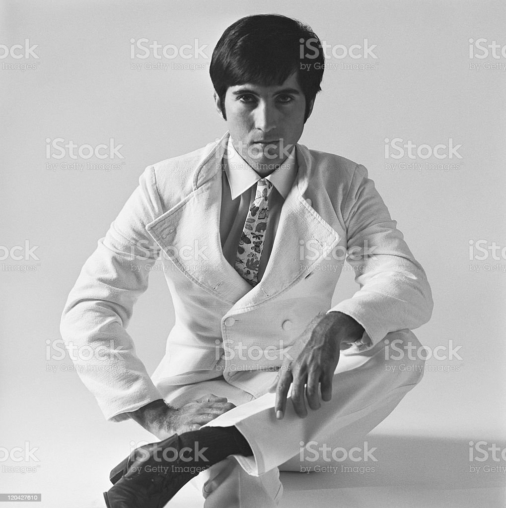 Young man sitting on white background, portrait stock photo