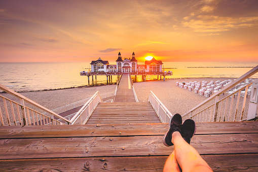 Young man sitting on wooden pier enjoying sunrise at Seebrucke Sellin, Baltic Sea, Germany