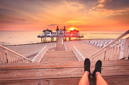 Young man sitting on wooden pier enjoying sunrise at Seebrucke Sellin, Baltic Sea, Germany