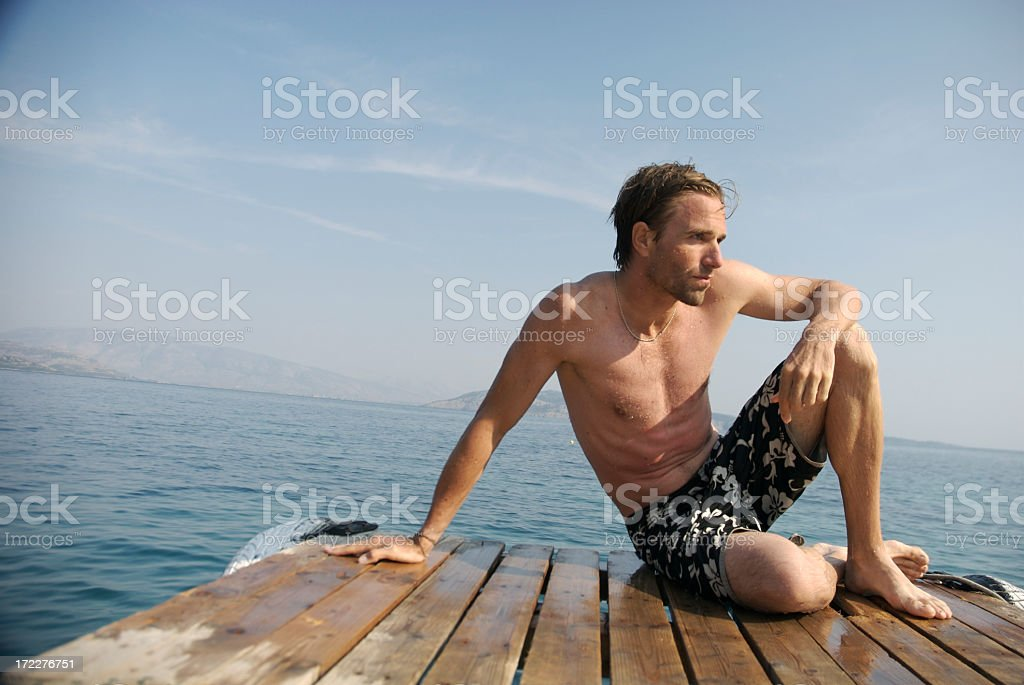 Young Man Sitting Outdoors on Wooden Dock in Surf Shorts royalty-free stock photo
