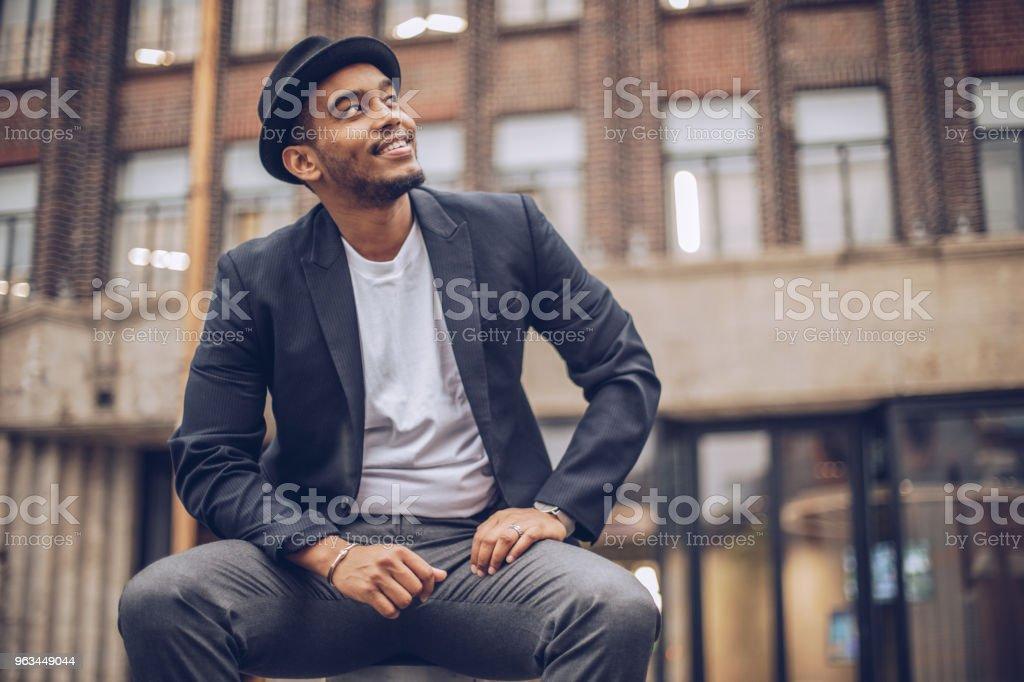 Jeune homme assis à l'extérieur - Photo de A la mode libre de droits
