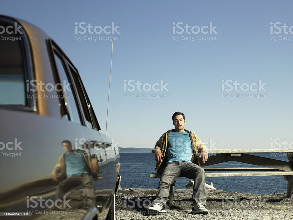 Young man sitting picnic table beside parked car, sea in background royalty-free stock photo