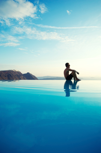 Man sits at the edge of an infinity pool reflecting bright Mediterranean skies