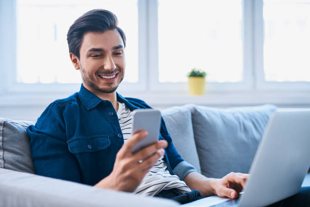 young man sitting relaxed on sofa with laptop and smartphone - guy sofa foto e immagini stock