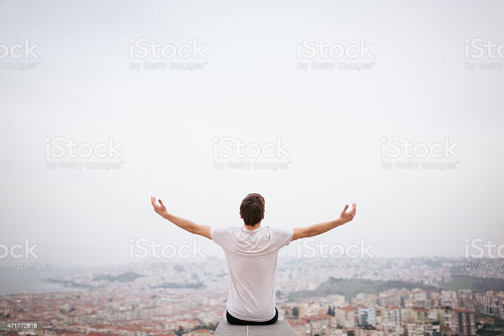 Young man sitting with cityscape stock photo