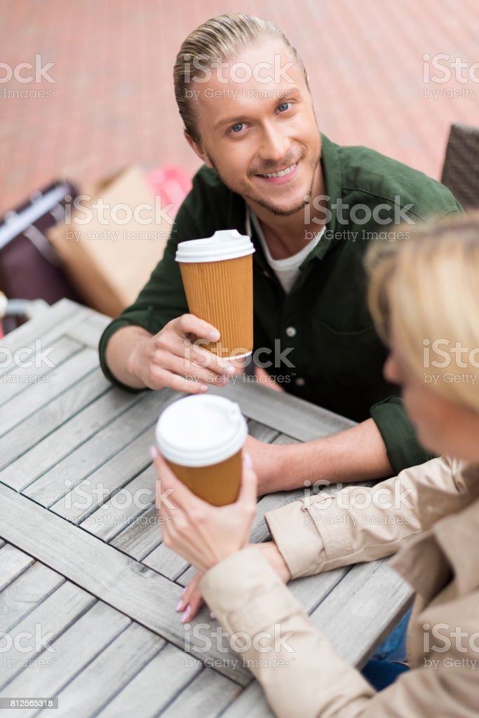 young man sitting with his girlfriend while drinking disposable coffee at cafe stock photo