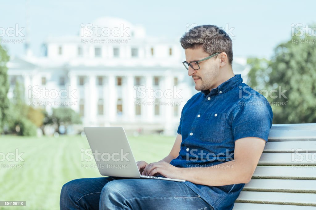 Young man sitting with laptop outside the office royalty-free stock photo