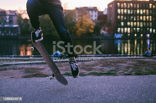 Young man skateboarding in Berlin by the Spree river. Close up image of the board. Taken on a nice Autumn day, just as the sun sets in Berlin's Friedrichshain - Kreuzberg district near the remaining parts of the Berlin Wall.