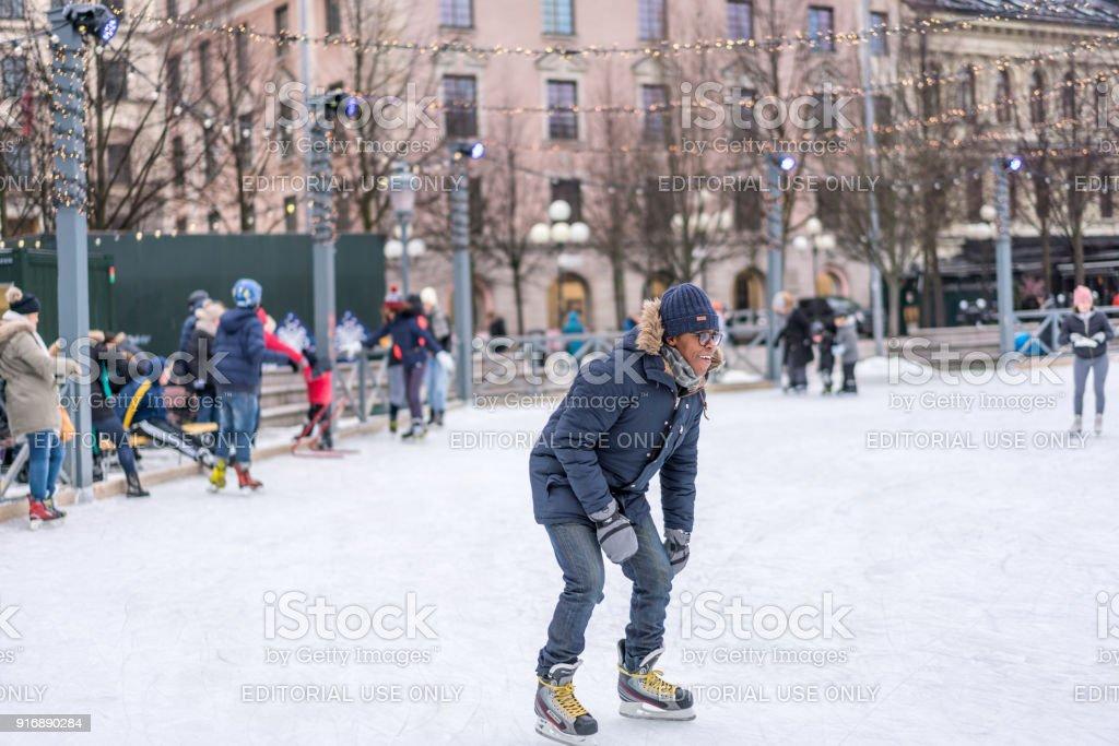 Young man skating at a public ice skating rink outdoors. stock photo