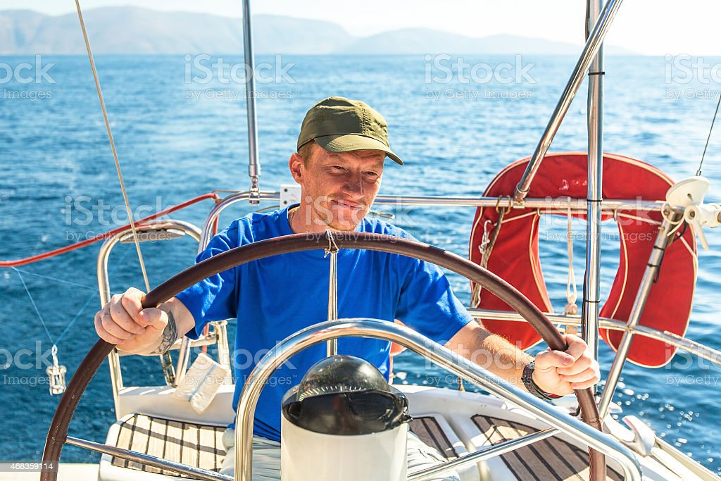 Young man skipper at the helm controls sailing yacht. royalty-free stock photo