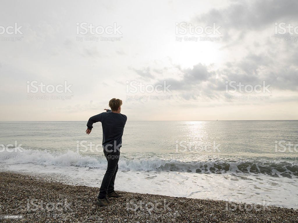 Young man skips rock into sea at sunrise stock photo