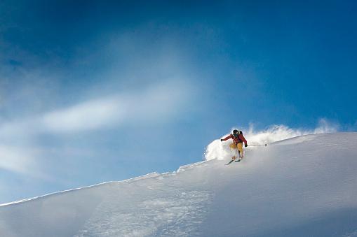 Young man skis off corniced ridge in powder snow