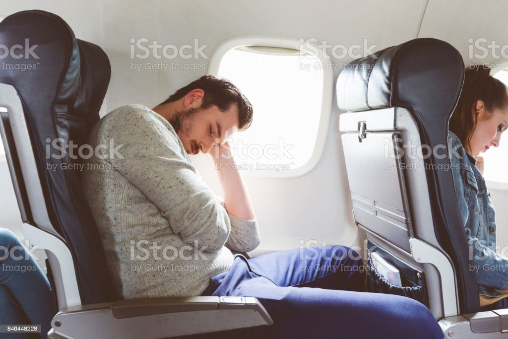 Young man sleeping during airplane journey stock photo