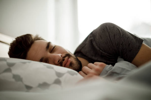 Young man sleeping in bed at home Young man sleeping in bed at home sleeping well stock pictures, royalty-free photos & images