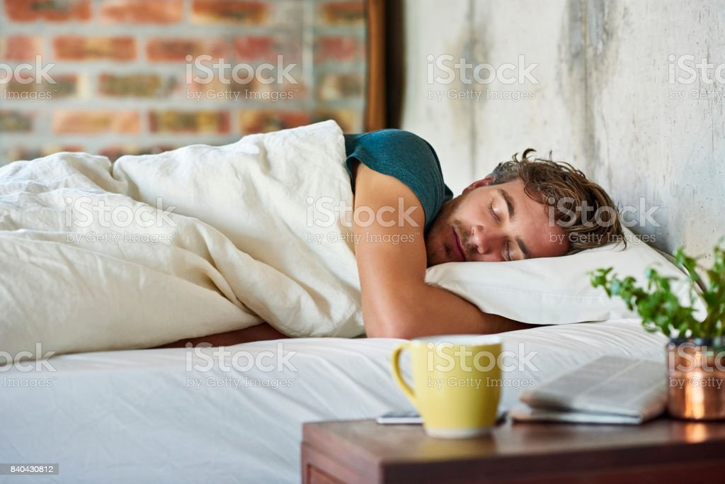 Young man sleeping in bed at home stock photo