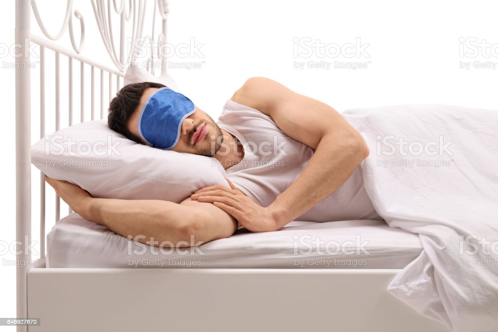 Young man sleeping in bed with an eye mask stock photo