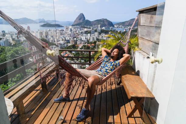 Young man sleeping in hammock on balcony in Rio stock photo