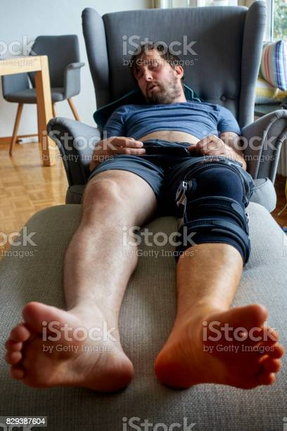 Young Man sleeping on the Couch with a Leg Brace on his Knee Young man sleeping on the couch while wearing a leg brace and compression knee sleeve. Accidents and Disasters Stock Photo
