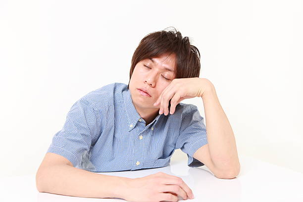 junger mann schlafen auf dem tisch - sandmann stock-fotos und bilder