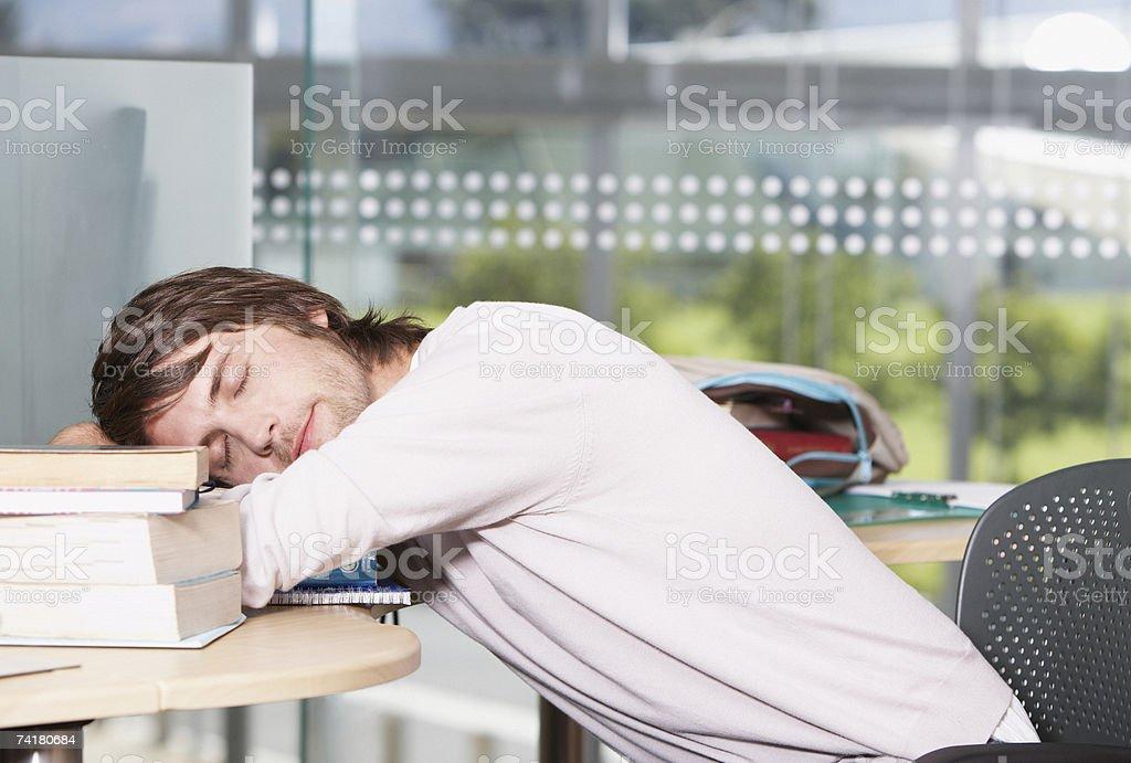 Jovem a dormir com livros na escola foto de stock royalty-free