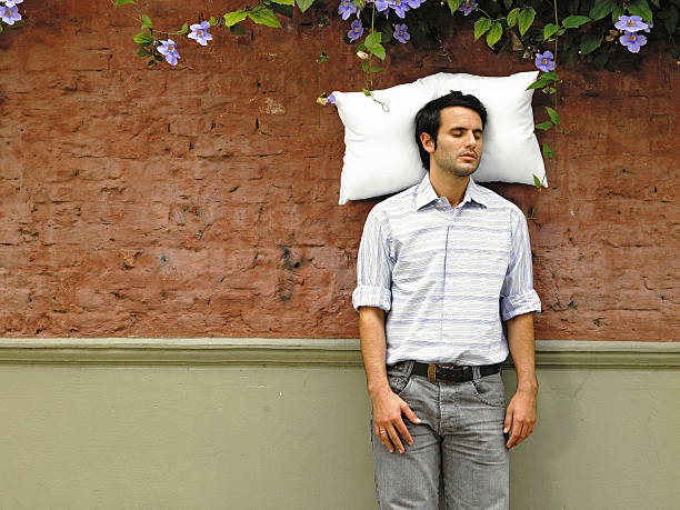 Young man sleeping with pillow against wall stock photo