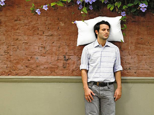 Junger Mann Schlafen mit Kissen von der Wand abprallen – Foto