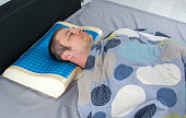 istock Young man sleeps in bed at home on latex pillow with memory and cooling effect. 1242068255