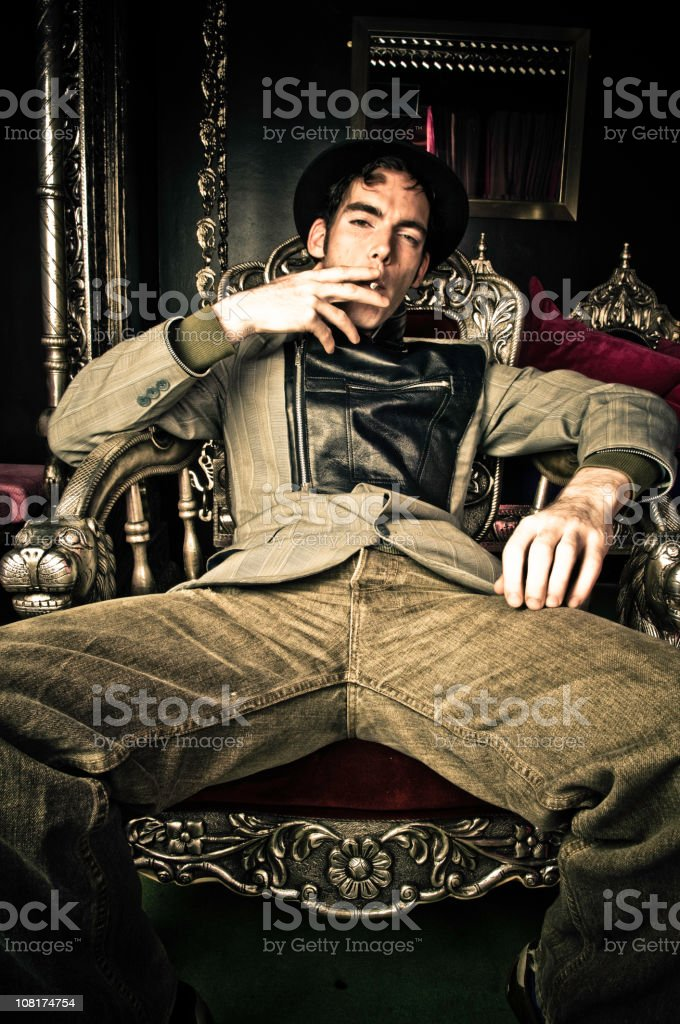 Young Man Slouching In Chair And Smoking Stock Photo