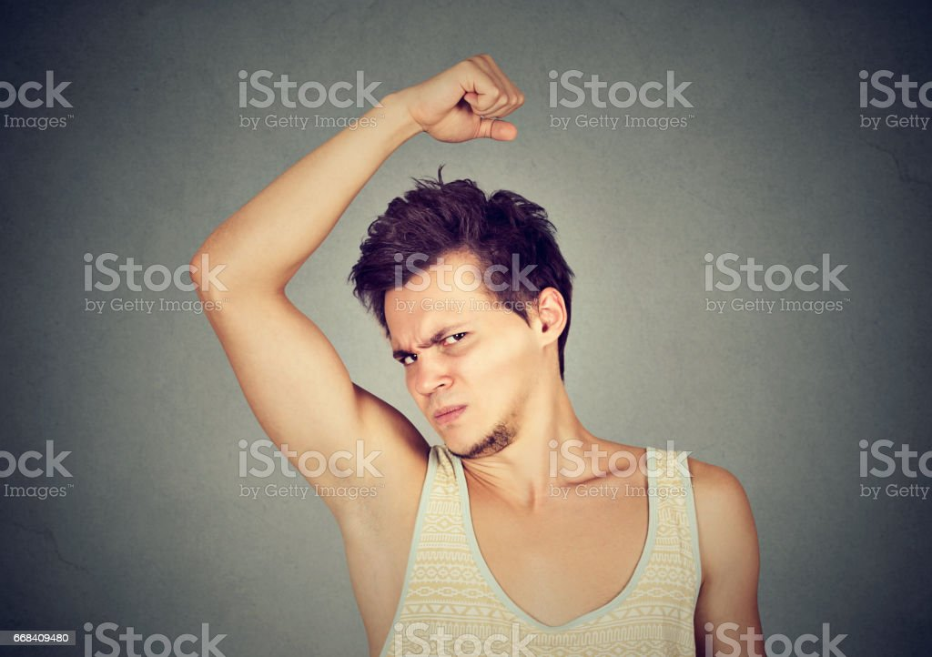 young man, smelling, sniffing his armpit, something stinks - Photo