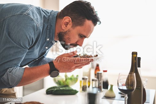 Good job. Side view portrait of handsome bearded gentleman holding plate with grilled meat