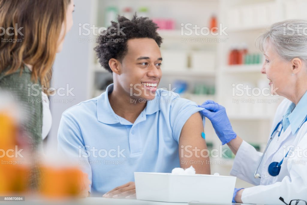 Young man smiles in relief at pharmacist after flu vaccination stock photo