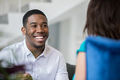 istock Young man smiles while talking with his counselor or psychiatrist in her office 1155988249