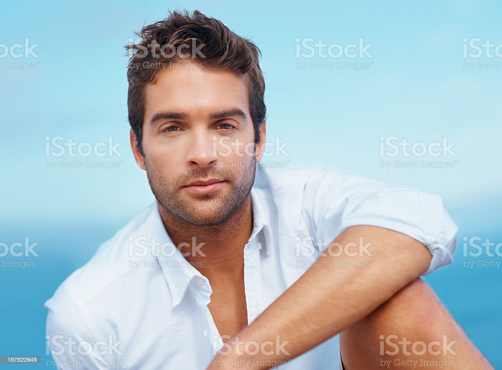 Young man smiling against the clear blue sky royalty-free stock photo