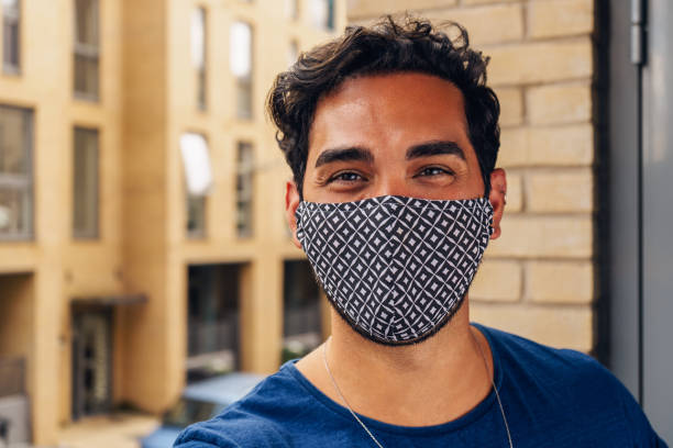 Young man smiling behind the mask during Covid-19 stock photo