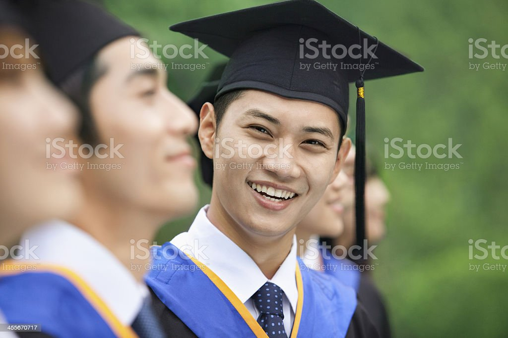 Young Man Smiling in a Row of University Graduates stock photo