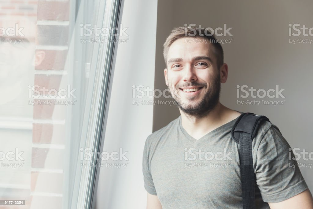 Young man smiling next to the window. stock photo