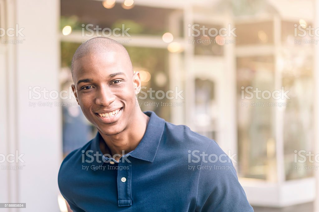 Young man smiling outside shop stock photo
