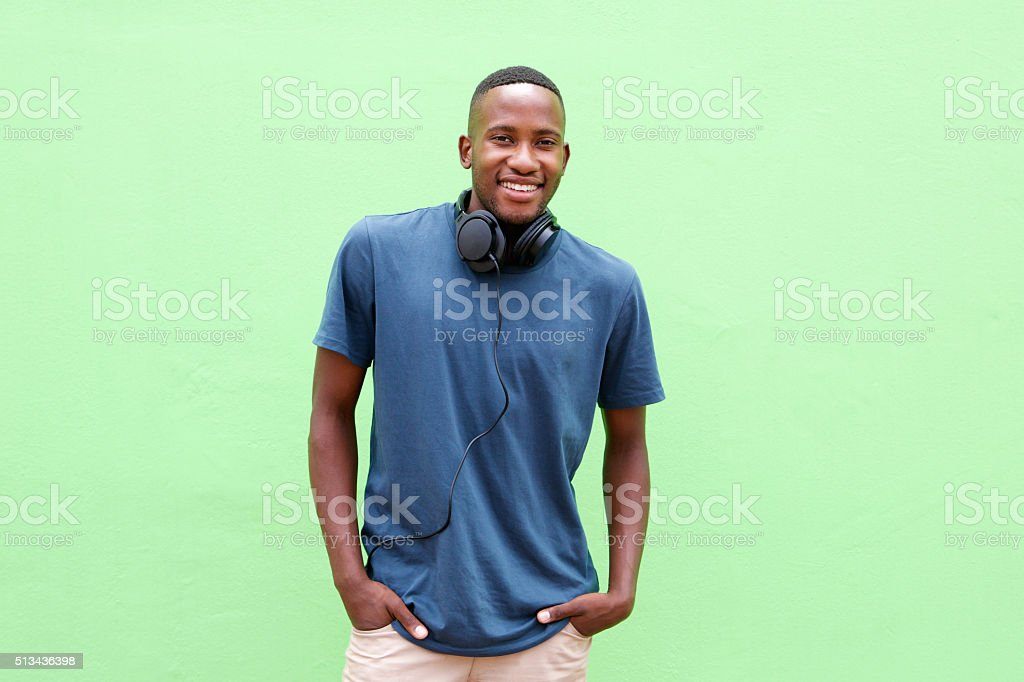 Young man smiling with headphones against green background stock photo