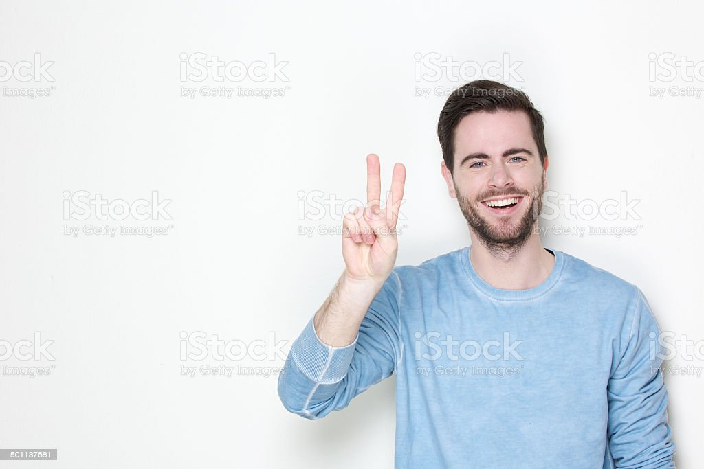 Young man smiling with victory sign stock photo