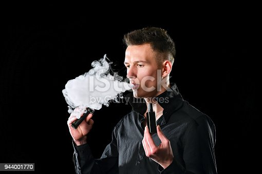 1033177506 istock photo Young man smoke E cigarette 944001770