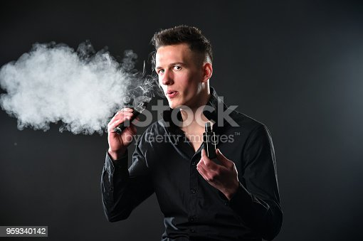 1033177506 istock photo Young man smoke electronic cigarette 959340142