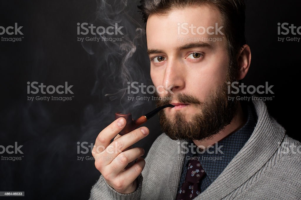 Young man smoking a pipe royalty-free stock photo